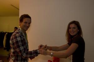 Camilla Rürup (intelliAd) übergibt ein Spendenarmband an Moritz Fahsig (Zieltraffic)